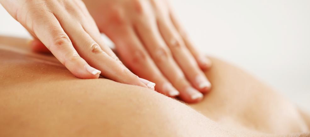 Hands press between the shoulder blades during a deep tissue massage.