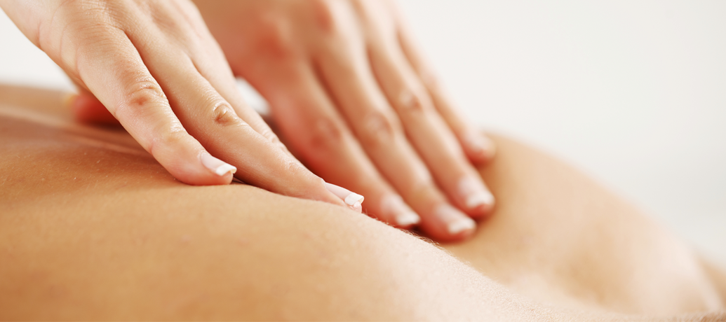 Hands press between the shoulder blades during a deep tissue massage.