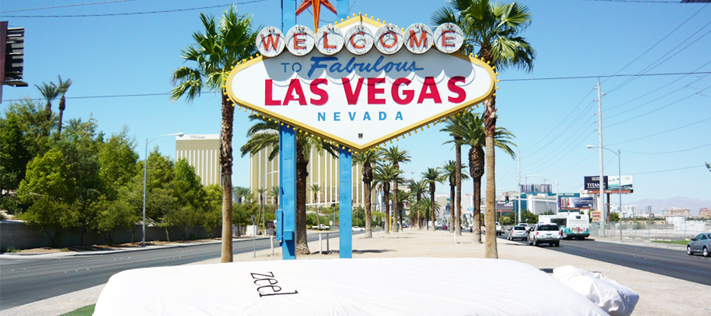 "Classic 'Welcome to Fabulous Las Vegas Nevada"" sign stands invitingly in the sun against palm trees"