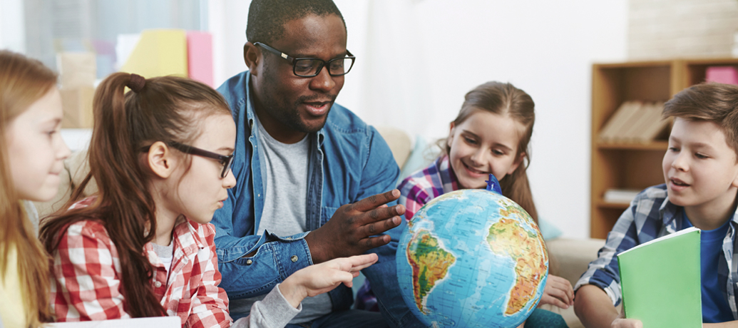 Teacher gathers a group of young students around a world globe during class.