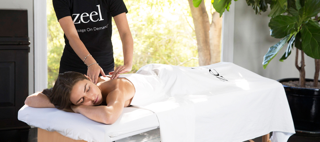 Woman relaxes on a massage table as she receives a luxury in-home massage experience from a Zeel Massage Therapist.