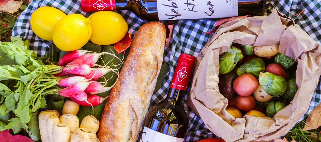 Fruits, vegetables, baguette, and wine are the perfect ingredients for an outdoor picnic.