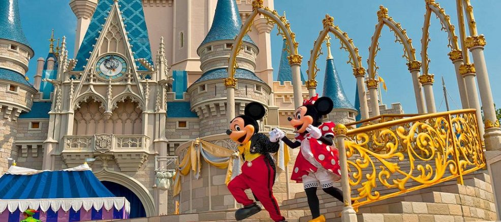 Mickey Mouse and Minnie Mouse run down the steps of Cinderella's Castle at Walt Disney World in Orlando, Florida.