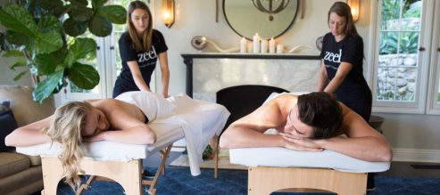 A man and woman enjoy a Zeel Couples Massage in the mini spa paradise created in their very own living room.