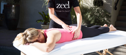 Athlete enjoys a Zeel Sports Massage in a relaxing, sunny outdoor setting.