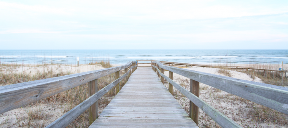 Beach boardwalk across sand dunes leads a view to the open blue water.