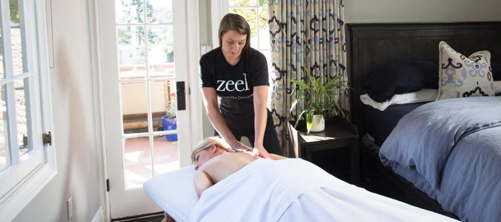Woman enjoys a relaxing Zeel massage in the comfort of her own bedroom.