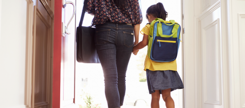 Child holds parent's hand as she prepares for her first day of school.