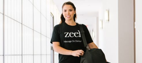 Smiling Zeel Massage Therapist heads to a booked appointment.
