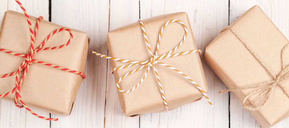 Gifts wrapped in kraft paper and packaged with striped twine bows are ready to be sent off for back-to-school gifts.