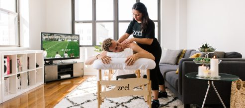 Man receives a massage in the comfort of his own apartment, while watching the big football game.