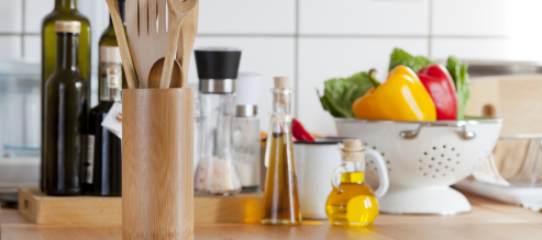 An assortment of wooden kitchen utensils and pantry ingredients fill a countertop.
