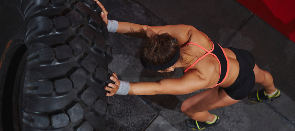 Female body builder expertly flips tire during intense workout