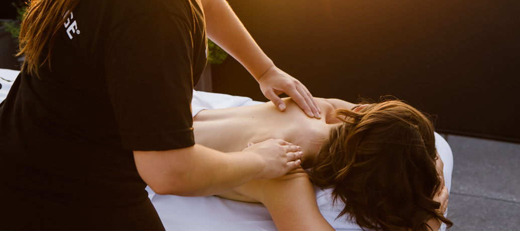A woman relaxes on a massage table as a licensed massage therapist works on the client's back.