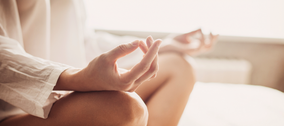 Hands are brought together in shuni mudra and rest on the knees of crossed legs during meditation.