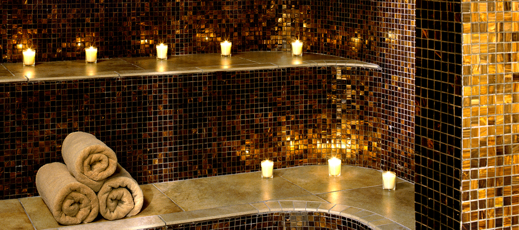 Warm light from lit candles sets the mood in a spa's steam room.