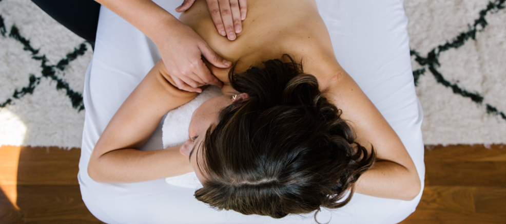A woman rests her head on her hands as she receives a relaxing back massage.