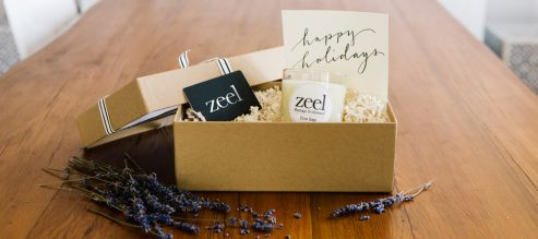 "An opened gift box reveals a Zeel gift card, a Dune Sage candle, and a card hand lettered with ""Happy Holidays""."