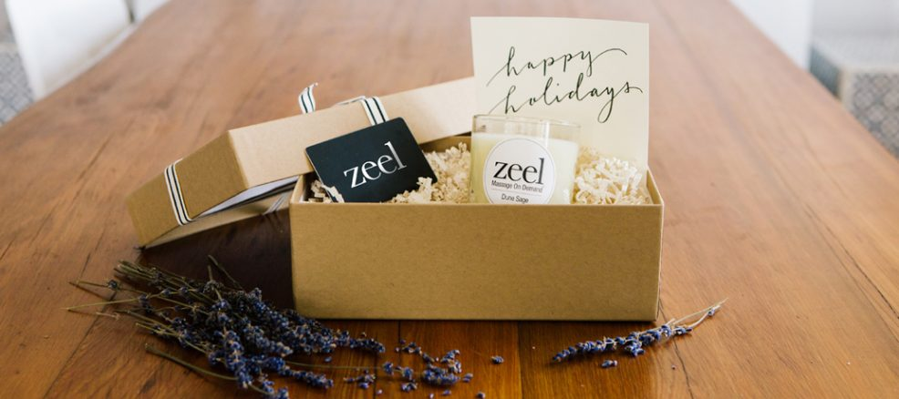 """An opened gift box reveals a Zeel gift card, a Dune Sage candle, and a card hand lettered with """"Happy Holidays""""."""