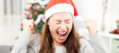 Girl in Santa hat screams and shakes her fists in the air with exasperation from holiday stress.