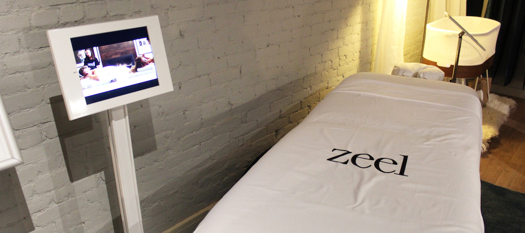 A massage table with Zeel sheets and an iPad with a Thrive Global app loaded await a client.