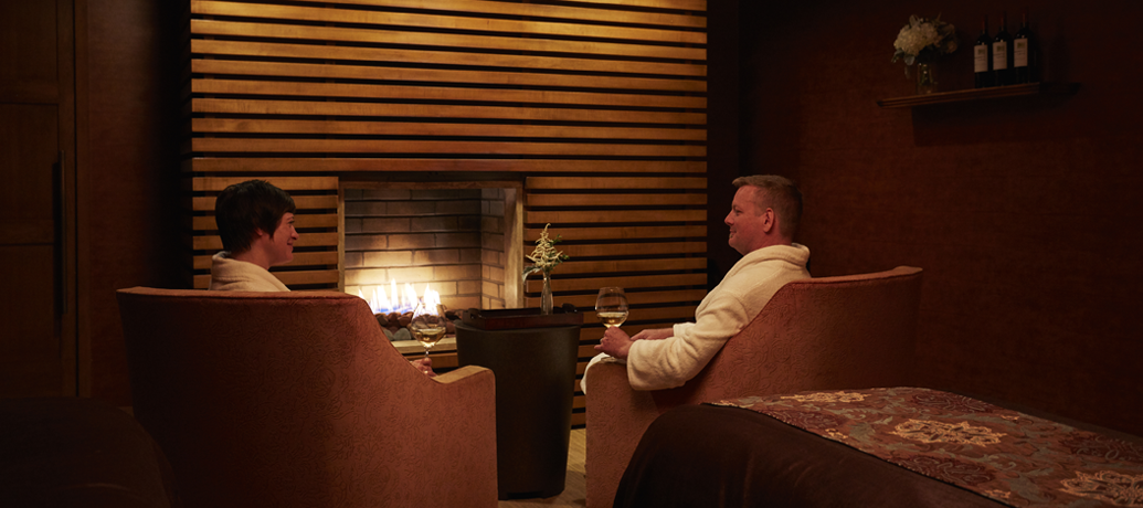 A couple relaxes with wine by the fire after a spa massage.