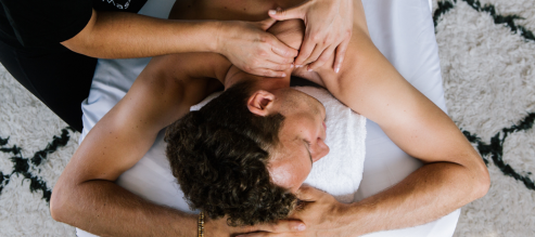 A man unwinds and rests his head on his hands while hands massage his shoulders and back atop a massage table.