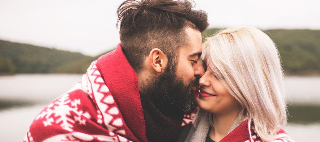 A hip man with a full beard and oversized red sweater leans in for a loving kiss from a sweetly smiling blonde.