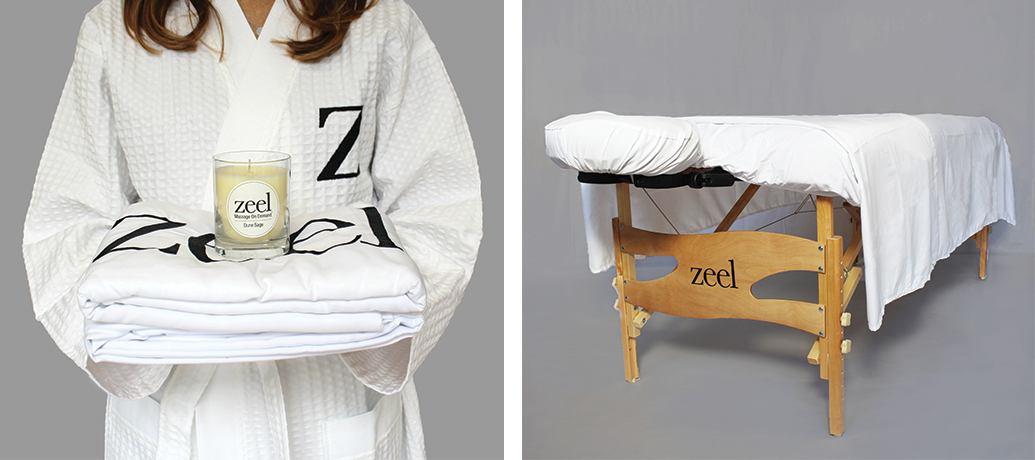 On the left, woman dressed in a white bathrobe embroidered with a black Z holds Zeel massage table sheets and a Zeel Dune Sage candle. On the right, a massage table stands on an angle with white sheets draped over top.