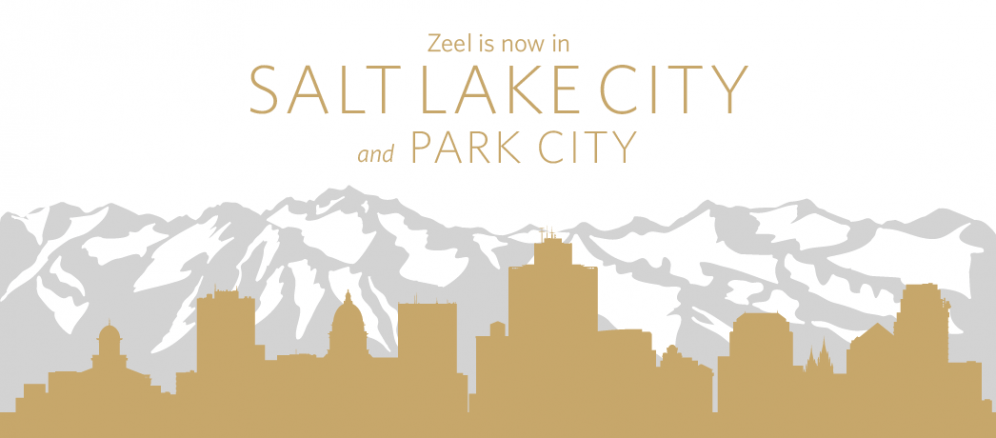 A graphic illustration of a city skyline silhouette in front of tall mountain peaks. The words 'Zeel is now in Salt Lake City and Park City' are printed across the top.