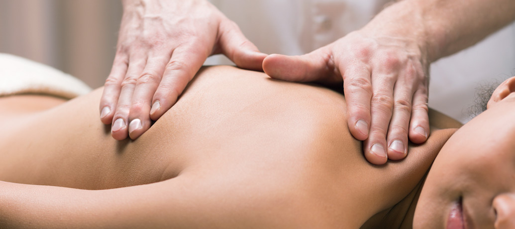 A male massage therapist's hands work into a client's back during a Zeel massage