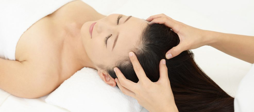 Woman gets scalp massage on table