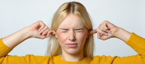 Young woman with tinnitus putting her fingers in her ears