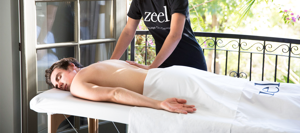 A man gets a massage in his home from Zeel Massage On Demand