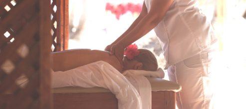 Woman giving a female customer a Zeel Massage on the beach