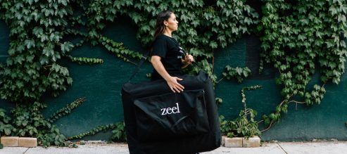 Zeel Massage Therapist carrying massage table