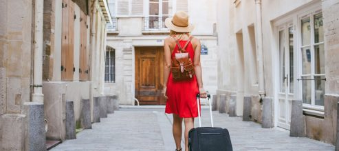 traveler on vacation with rolling suitcase