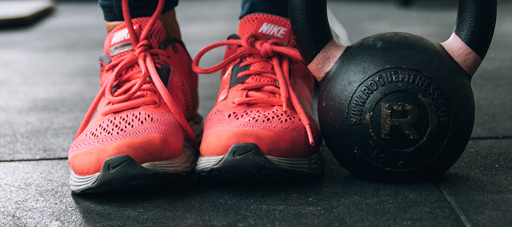 Sneakers and barbell at gym