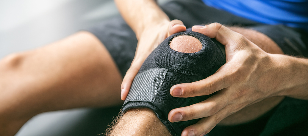 Man with knee pain wearing knee brace