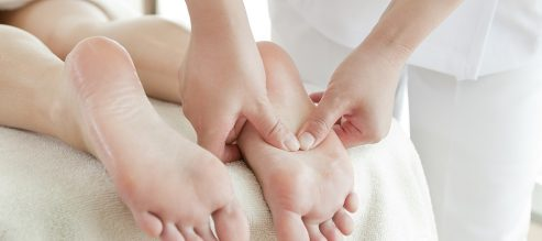 applying pressure to feet with reflexology table massage